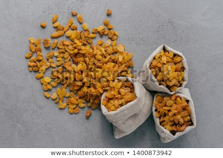 Burlap sacks with dry raisins spilled out over grey texture background. View from above. Dried fruit Stock photo © vkstudio