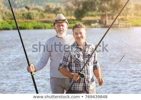 senior man with fishing rod or spinning on river Stock photo © dolgachov