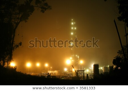 oil rig in the mist illuminated at night stock photo © justinb