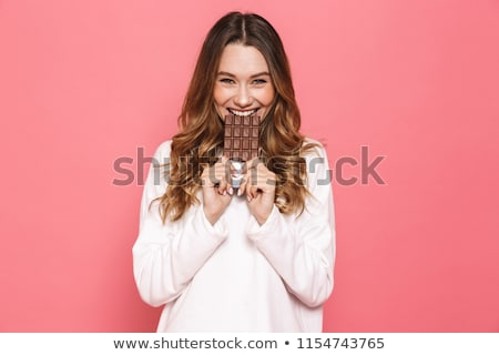 beautiful woman biting in to chocolate stock photo © stryjek