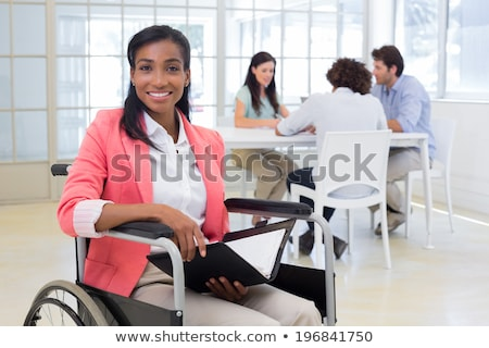 Young woman in wheelchair working with a male colleague Stock photo © photography33