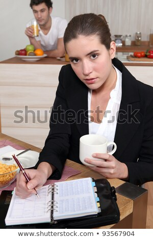 young businesswoman eating her breakfast and looking at her agenda Stock photo © photography33