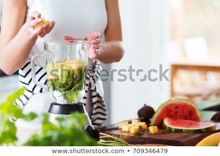 Young woman preparing vegetables in the blender Stock photo © julief514