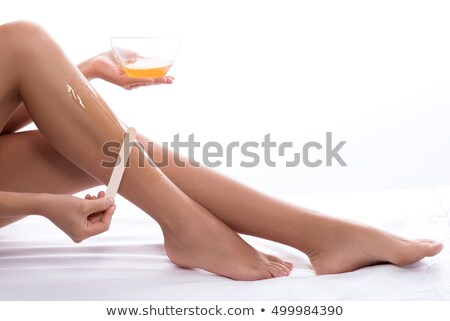 Gyönyörű nő gyantázás lábak ül kanapé fehér Stock fotó © AndreyPopov