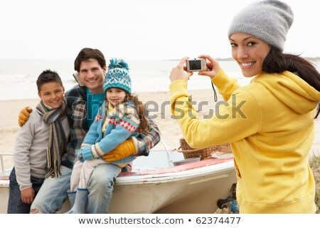 mother taking family photograph on winter beach stock photo © monkey_business