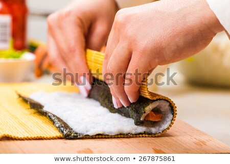 hands turns nori sheet with filling  Stock photo © OleksandrO