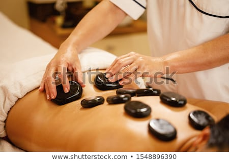 placing hot stones during massage stock photo © sumners