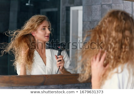 happy attractive woman in bathrobe standing and using hair dryer stock photo © deandrobot