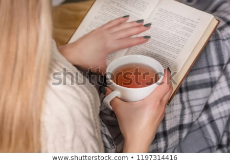 close up of young woman reading book in bed stock photo © nobilior