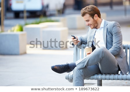 smiling man using mobile phone and drinking coffee outdoors stock photo © deandrobot