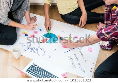 Three people writing observations during brainstorming session Stock photo © Kzenon