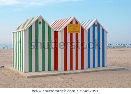 multi colored wooden beach huts on sand stock photo © wavebreak_media