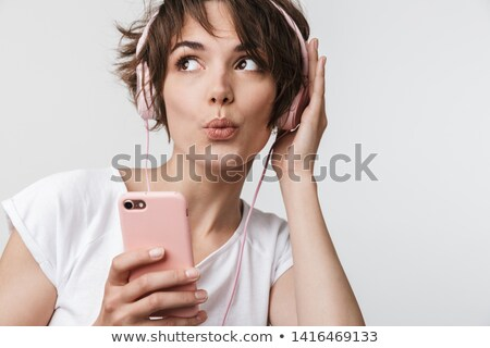 Gorgeous young caucasian lady posing over white wall. Stock photo © deandrobot
