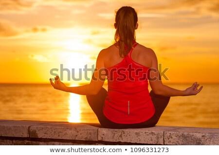 Yoga girl meditating and relaxing in yoga pose, ocean view Stock photo © blasbike