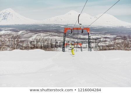 Happy young woman with snowboard in front of volcanos Stock photo © MikhailMishchenko