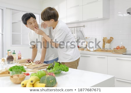 Foto d'archivio: Homosexual Couple Eating Breakfast Cooking In Kitchen