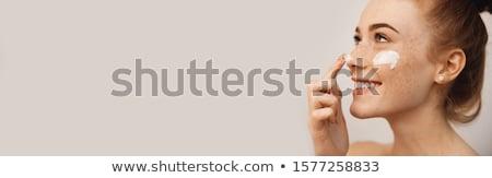 Lány jelentkezik hidratáló krém izolált fehér Stock fotó © svetography