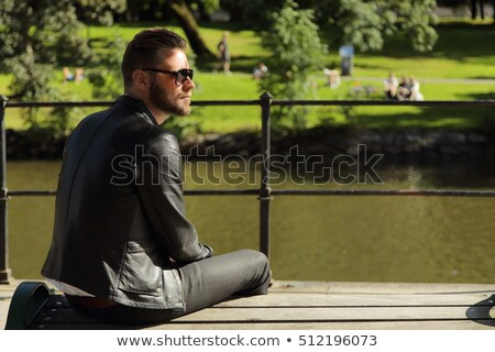 man in leather jacket sits and looks up to side Stock photo © feedough