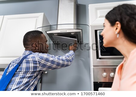 Repairman Fixing Kitchen Extractor Filter Over Kitchen Counter Stock photo © AndreyPopov