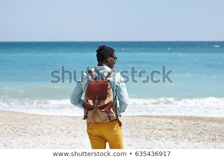 Excited young african man with backpack outdoors Stock photo © deandrobot