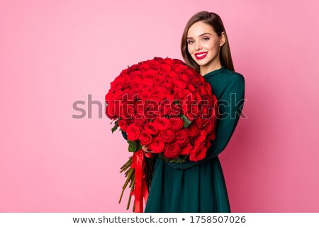 Happy young brunette in red dress holding big bunch of red roses. Stock photo © studiolucky