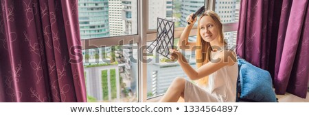 woman sits by the window and uses an electronic hairbrush banner long format stock photo © galitskaya