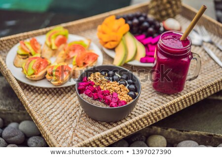 breakfast on a tray with fruit buns avocado sandwiches smoothie bowl by the pool summer healthy stock photo © galitskaya