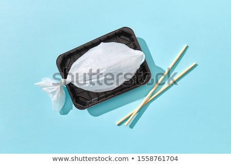 Dinner container with fish from plastic bag served wooden chopsticks. Stock photo © artjazz