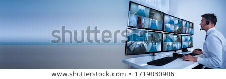 Security System Operator Looking At CCTV Footage At Desk Stock photo © AndreyPopov
