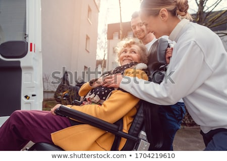 Senior woman in wheelchair being picked up by transport service Stock photo © Kzenon