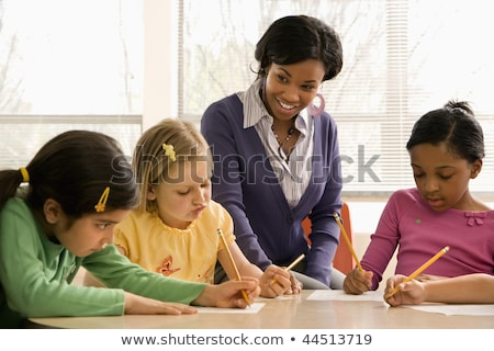 teacher helping students in school classroom horizontally frame stock photo © hasloo
