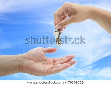 Woman Handing Over Key Against A White Background Stok fotoğraf © vichie81