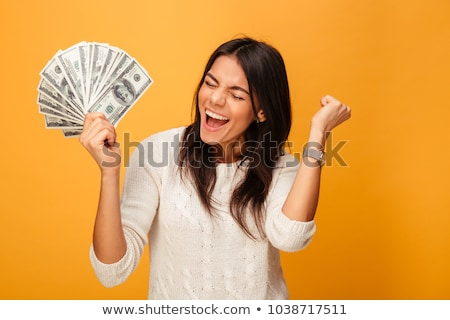 Portrait of pretty young woman holding a fan of dollar bills Stock photo © rozbyshaka