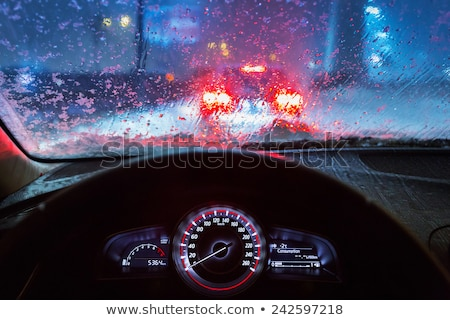 Stock photo: Car driving in a rain storm with blurred red lights