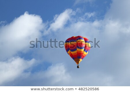 Orange and yellow hot-air balloon floating among clouds Stock photo © Balefire9