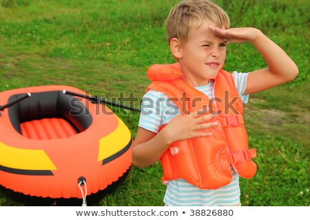 boy keeps watch and inflatable boat on lawn Stock photo © Paha_L
