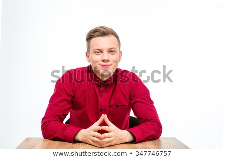 Content handsome young man in red shirt sitting and smiling Stock photo © deandrobot
