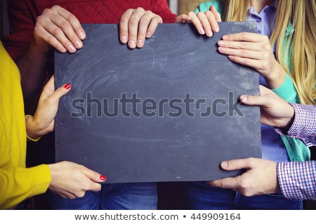 group of young business partners with blank blackboard sign stock photo © dashapetrenko