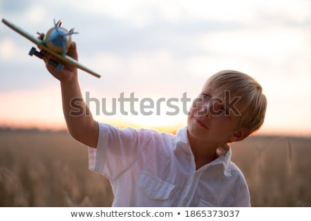 children play against the sun on summer sunset with airplane in stock photo © zurijeta