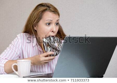 Woman eating sesame bagel in office Stock photo © stevanovicigor