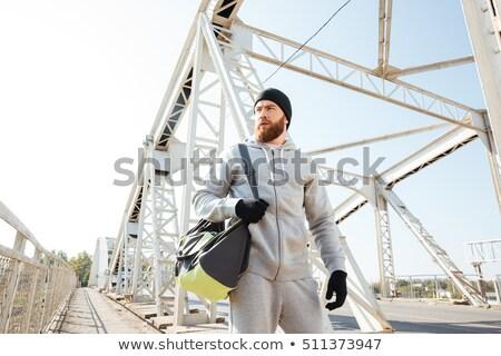Young bearded sports man with bag walking along urban bridge Stock photo © deandrobot
