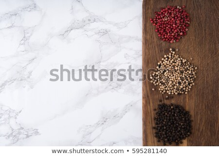 Spicy white peppercorns heap on a wooden cutting board Stock photo © deandrobot