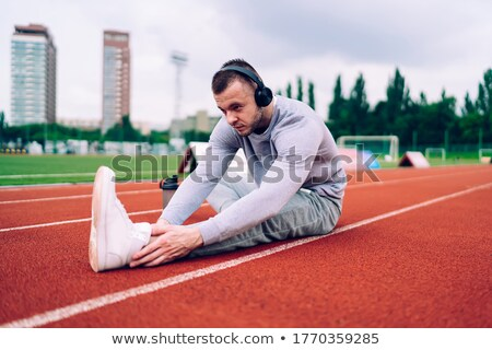 Healthy serious sportsman listening to music while running Stock photo © deandrobot