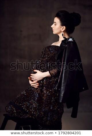 side view of smiling brunette woman holding jacket on shoulder stock photo © deandrobot
