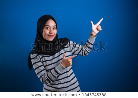 smiling young woman student presenting with her palm to side stock photo © feedough