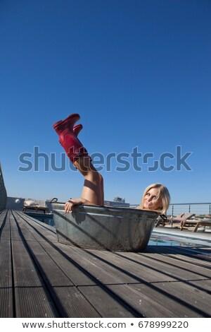 Woman wearing rainboots in metal tub Stock photo © IS2