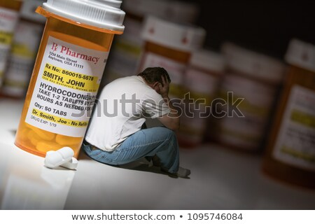 Man Holding Head Sitting Next To Hydrocodeon Pills and Bottle Stock photo © feverpitch