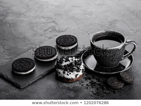 Black coffee cup with saucer and doughnut with black cookies on black stone kitchen table background Stock photo © DenisMArt