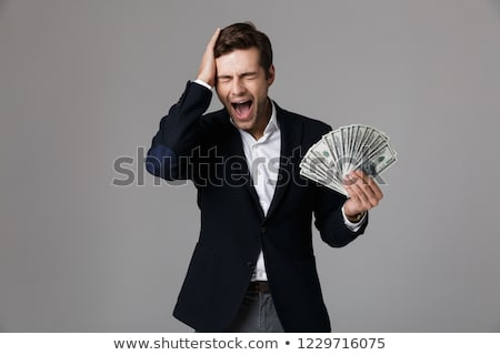 Image of excited businessman 30s in suit holding fan of money an stock photo © deandrobot