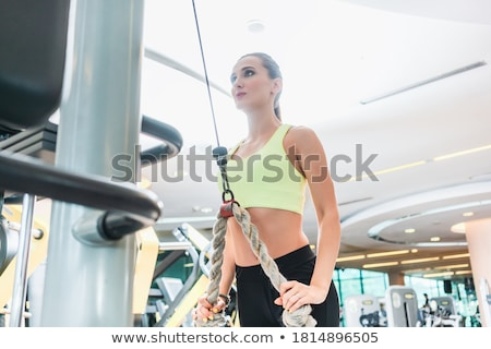 low angle view of a beautiful fit woman exercising with cable rope stock photo © kzenon